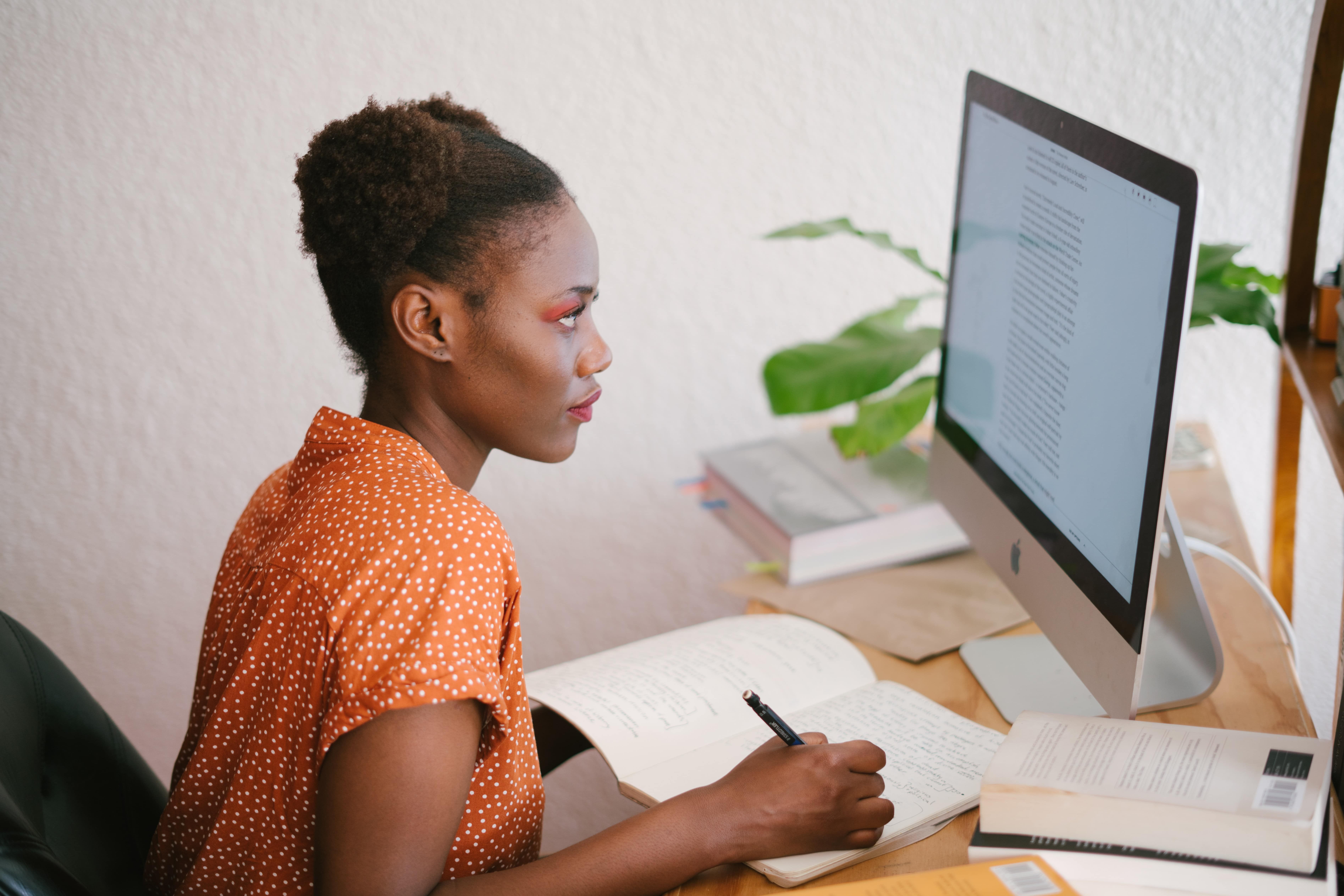 Woman working on computer and note book.